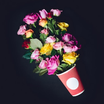 Gorgeous bouquet of colorful roses put in red paper cup