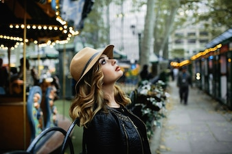 Gorgeous lady in beige hat looks up in the sky standing on the street