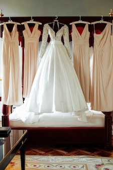 Gorgeous wedding dress and beige gowns for bridesmaids hang over the bad