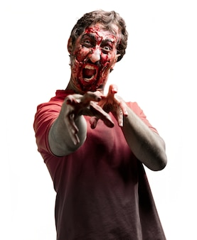 Gory zombie screaming with raised arms