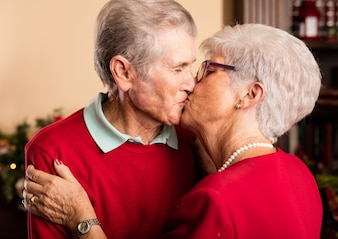 Granparents kissing each other on christmas