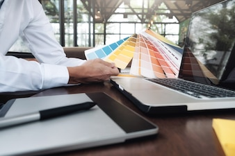 机の上にグラフィックデザインとカラースウォッチとペン。作業工具とアクセサリーを使用した建築図面