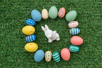 Grass background with easter bunny surrounded by colored eggs