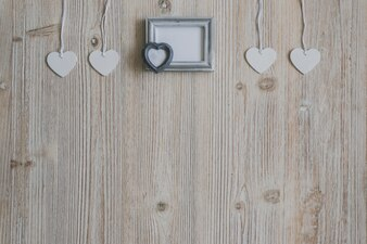 Gray photo frame and hearts hanging on ropes