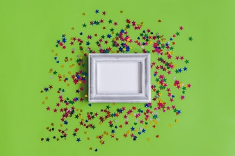 Gray photo frame with confetti on a green background