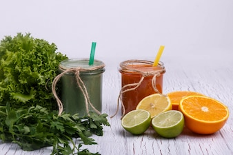 Green and orange detox coctails stands on white table with fruits and vegetables