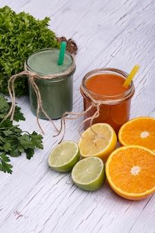 緑色とオレンジ色のデトックス・コクツールが果物と野菜の白いテーブルの上に立つ