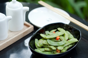 Green beans with red chilli in black ceramic bowl