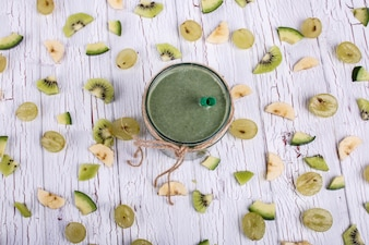 Green detox coctail stands on table with small pieces of fruits