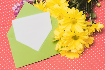 Green envelope with piece of paper and yellow daisies