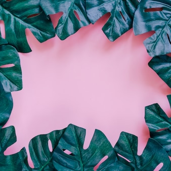 Green palm leaves frame on pink background for poster or template design