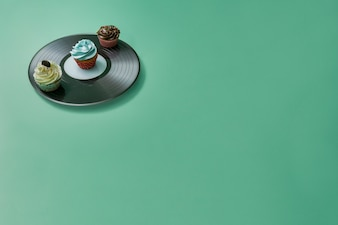 Green surface with vinyl and cupcakes