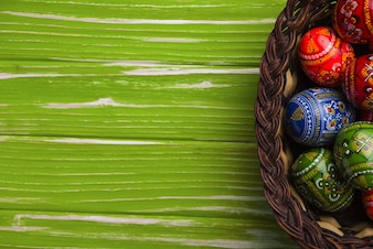 Green wooden surface with basket and easter eggs