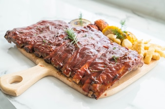 Grilled rib pork with barbecue sauce and vegetable and frech fries on wooden cutting board