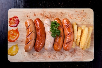 Grilled sausage with chili powder and french fries and parsley on top of sausage on wooden block on black table.