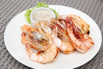 Grilled shrimps with seafood sauce on white plate