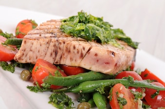 Grilled tuna steak with vegetables closeup