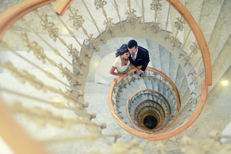 Groom and bride on a spiral staircase