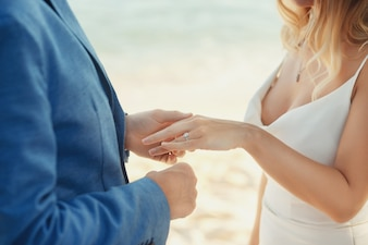 Groom in blue suit puts wedding ring on bride's hand standing on