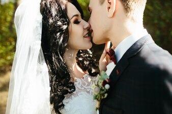 Groom kissing bride in woods