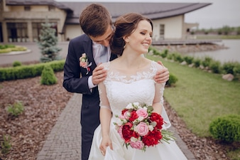 Groom touching the shoulders of his smiling wife