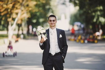 Groom with a bouquet in a park