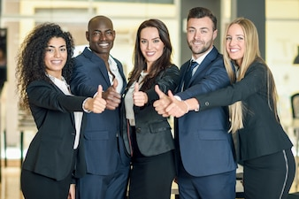 Group of businesspeople with thumbs up gesture in modern office. Multi-ethnic people working together. Teamwork concept.