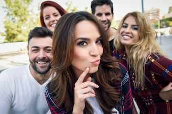 Group of friends in a selfie with a girl in the middle putting kiss face