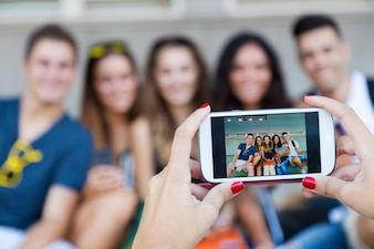 Group of friends taking photos with a smartphone in the street.