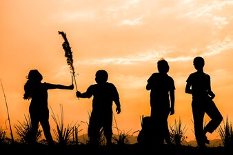 夕日、シルエットで牧草地で遊んでいる幸せな子供たちのグループ