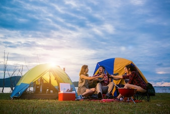 Group of man and woman enjoy camping picnic and barbecue at lake with tents in background. Young mixed race Asian woman and man. Young people's hands toasting and cheering bottles of beer.