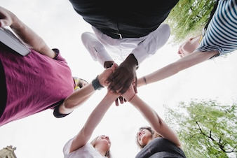 Group of people holding hands together