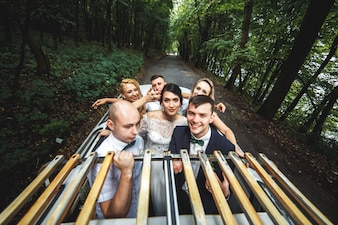 Group of people in car celebrating wedding