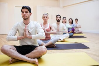 Group of people sitting in lotus position