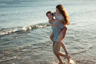 Guy carrying girlfriend at the shoreline