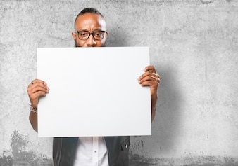 Guy holding a blank poster with wall background