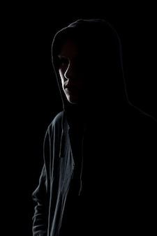 Guy in hooded sweatshirt in the dark