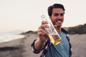 Guy with bottle of beer at the beach