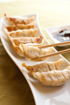 Gyoza and chopsticks on white plate