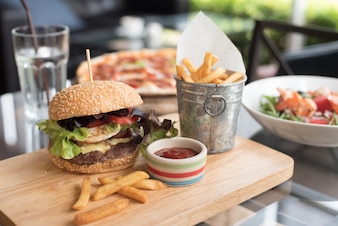 Hamburger on a wooden board with french fries