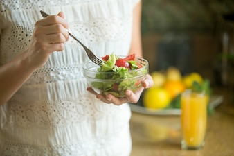 Hand holding a bowl with salad, fork in another