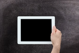 Hand holding a tablet with blackboard background