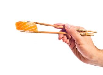 Hand holding sushi with chopsticks