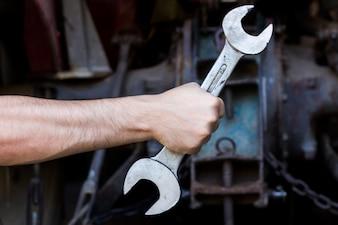 Hand holding wrench on dark background