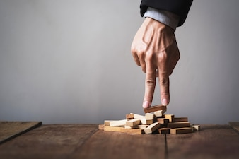 Hand liken business person stepping up a toy wooden block to goal