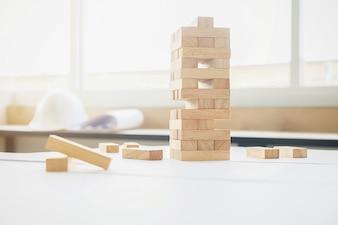 ビジネスマンの計画、リスクとビジネスの戦略。ビジネスマンは塔に木ブロックを配置して賭ける。