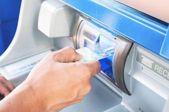 人の手がATMマシンにカードを挿入する
