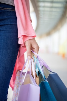 Hand of young woman holding shopping bags