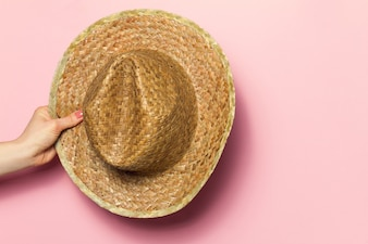 Hand of young woman holding summer straw hat on pink background. Fashion Background. Summer Concept.