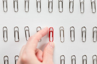 Hand picking among metal paperclips one red, different from others